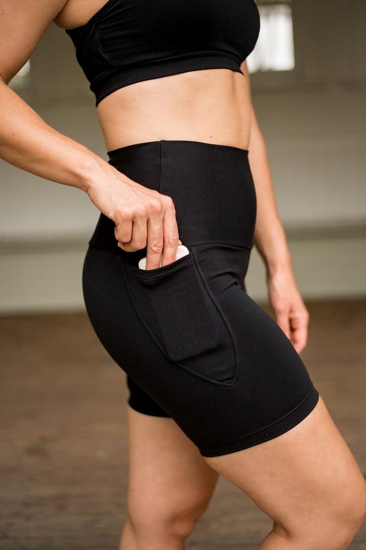 High waist black beauty pocket mid shorts close up with phone